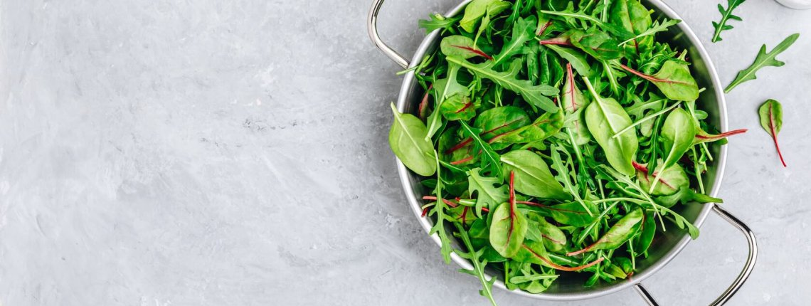 Mix of spring fresh leaves with arugula, lettuce, spinach, beets. Ingredients for salad on a gray stone background.