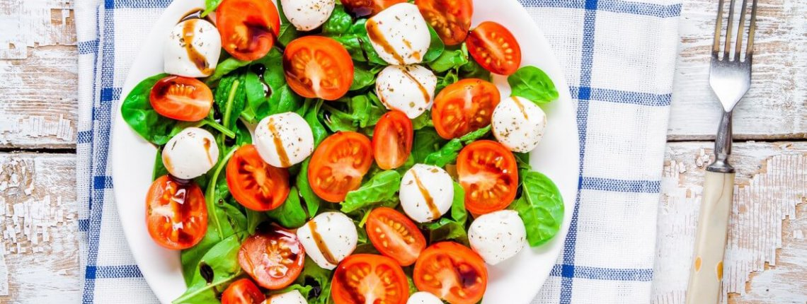 salad of mozzarella, cherry tomatoes and spinach with balsamic sauce on a white rustic table