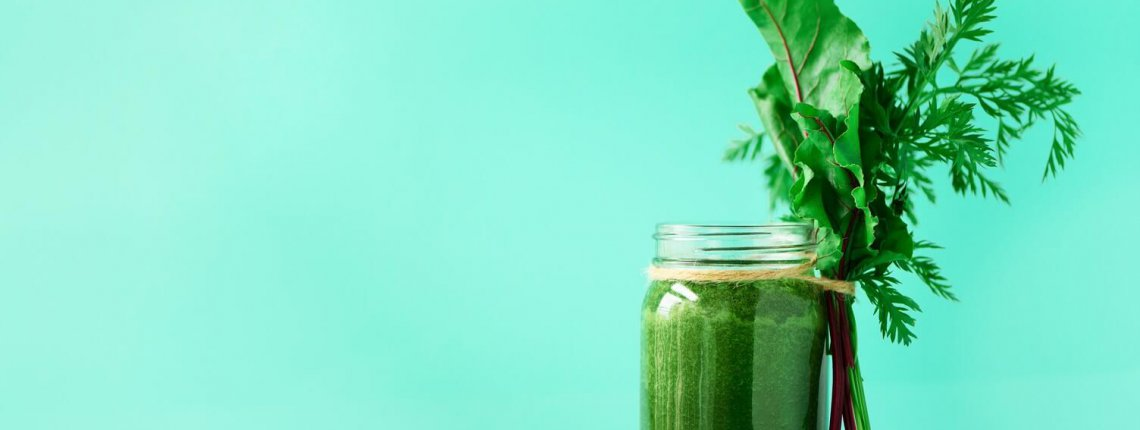 Smoothie with beet greens and carrot tops on blue background, copy space. Summer vegan food concept. Healthy detox eating, alkaline diet. Fresh squeezed juice, drink from vegetables. Leafy greens